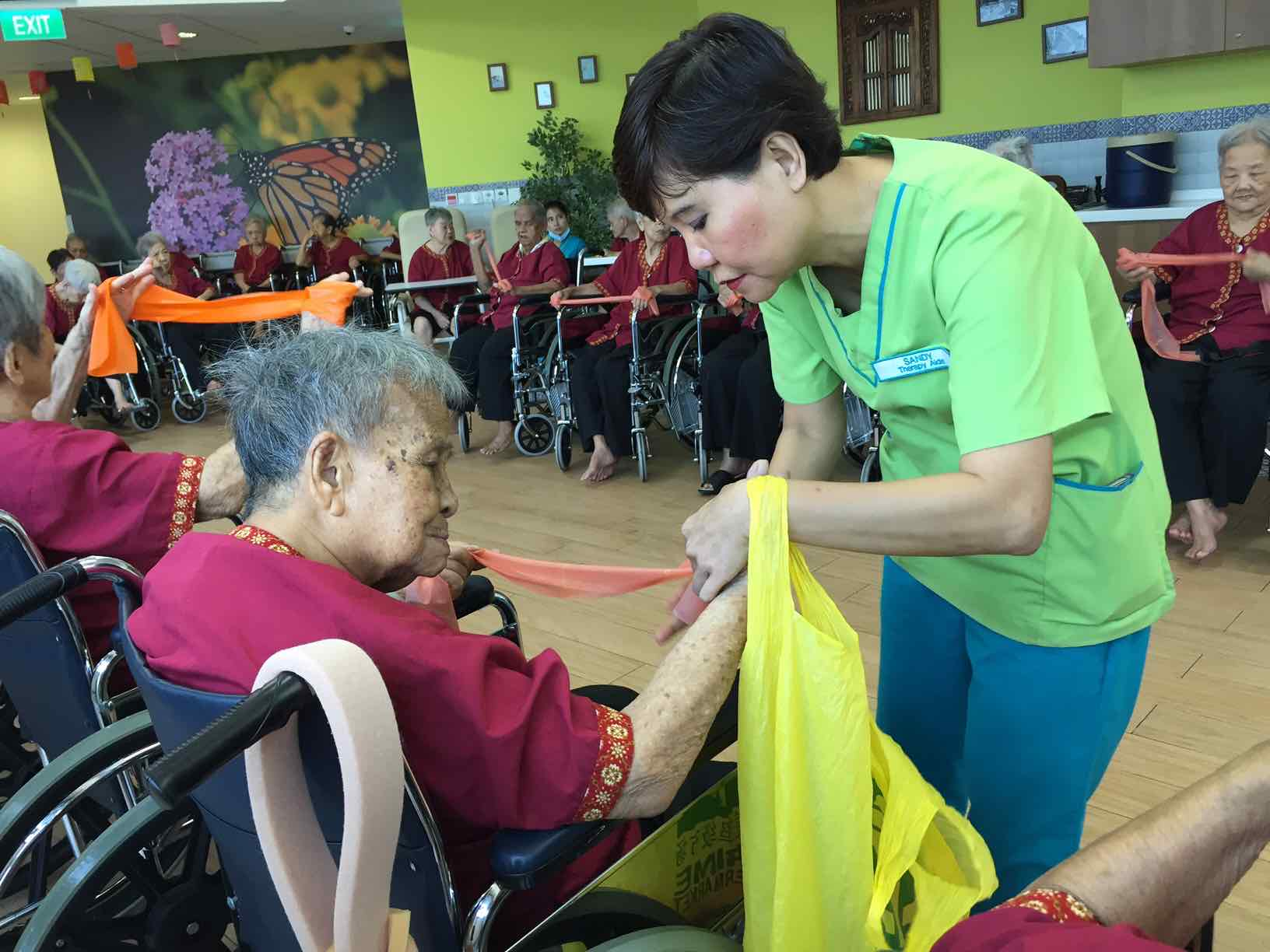 sandy-helping-elderly-tie-their-therabands-at-ntuc-health-nursing-home-aspirantsg